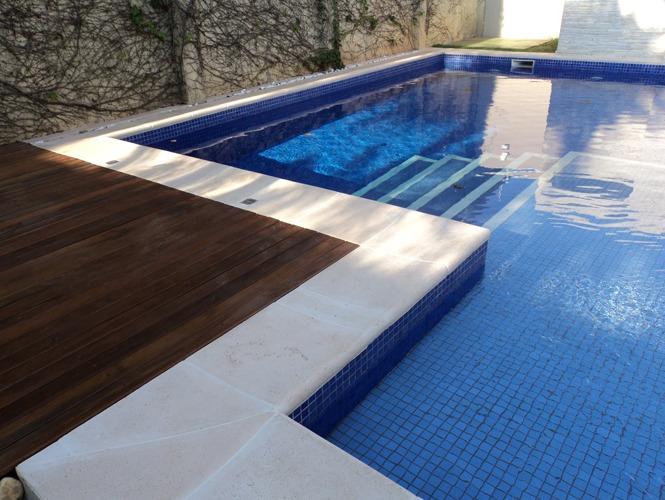 Borda de piscina com pedra e piso de madeira