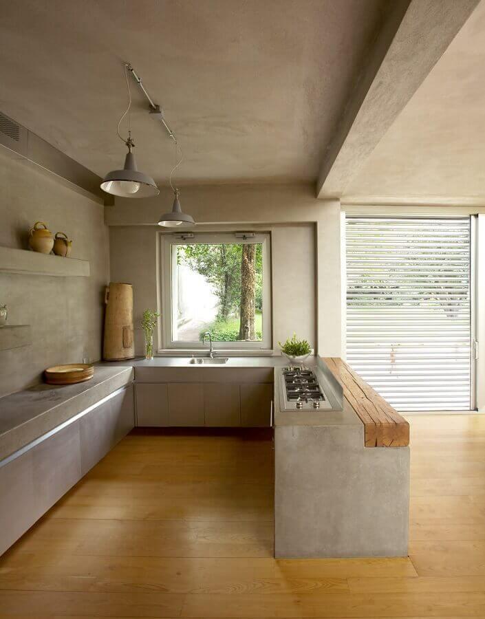 cozinha conceito aberto feita em cimento queimado com piso de madeira Foto Zozu