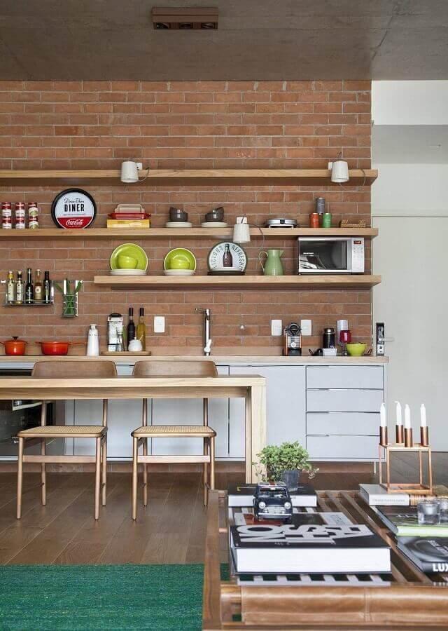 parede de tijolinho a vista com prateleiras de madeira para decoração de cozinha conceito aberto Foto Migs Arquitetura