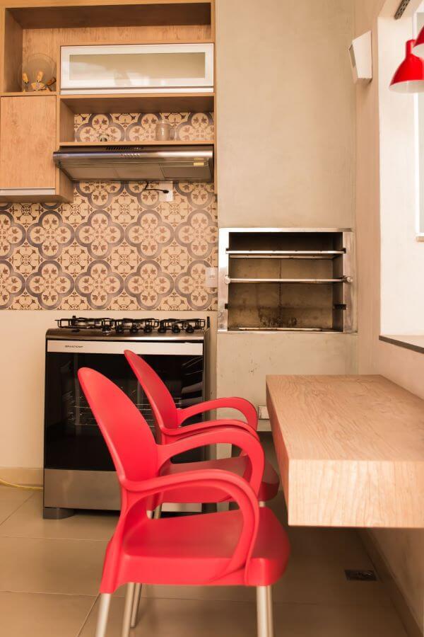Varanda com churrasqueira e cadeiras vermelhas