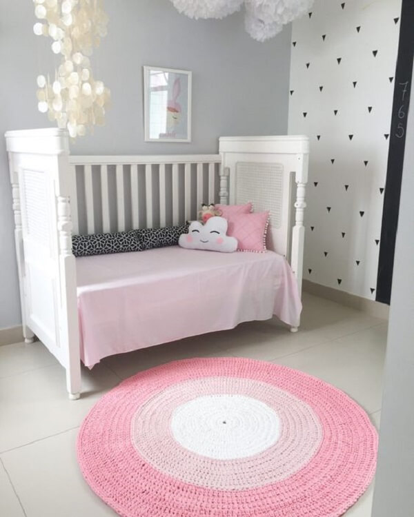 Quarto de bebê clean com tapete rosa redondo