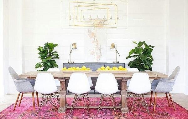 O tapete rosa da sala de jantar delimita o espaço das refeições