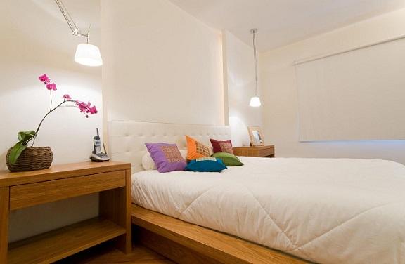 Almofadas decorativas colorida em quarto claro Projeto de Leticia Araujo