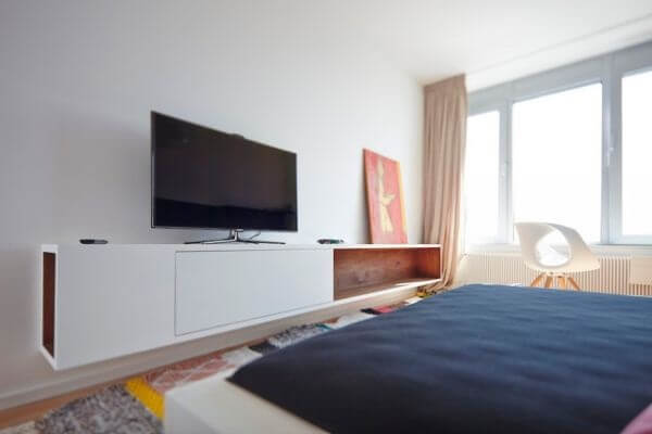 No quarto de casal a bancada suspensa serve de apoio para a televisão