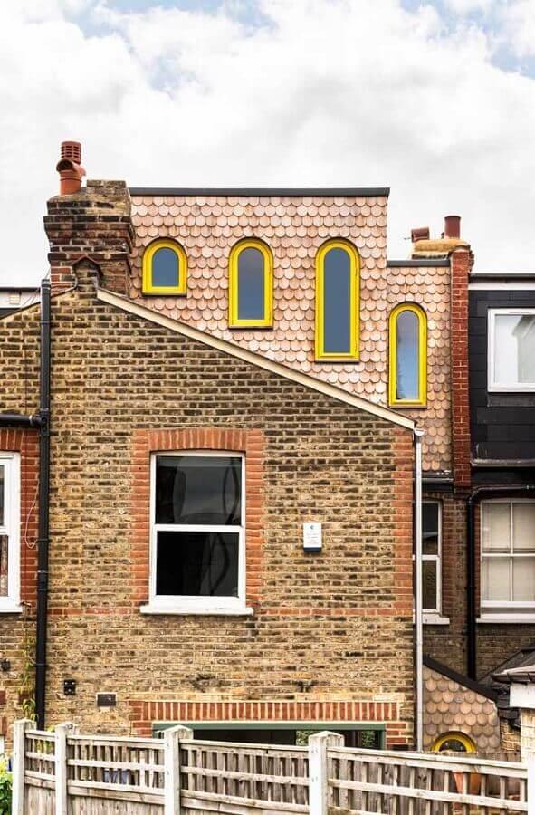 fachada de tijolinho a vista decorada com janelas amarelas  Foto HomeNotes