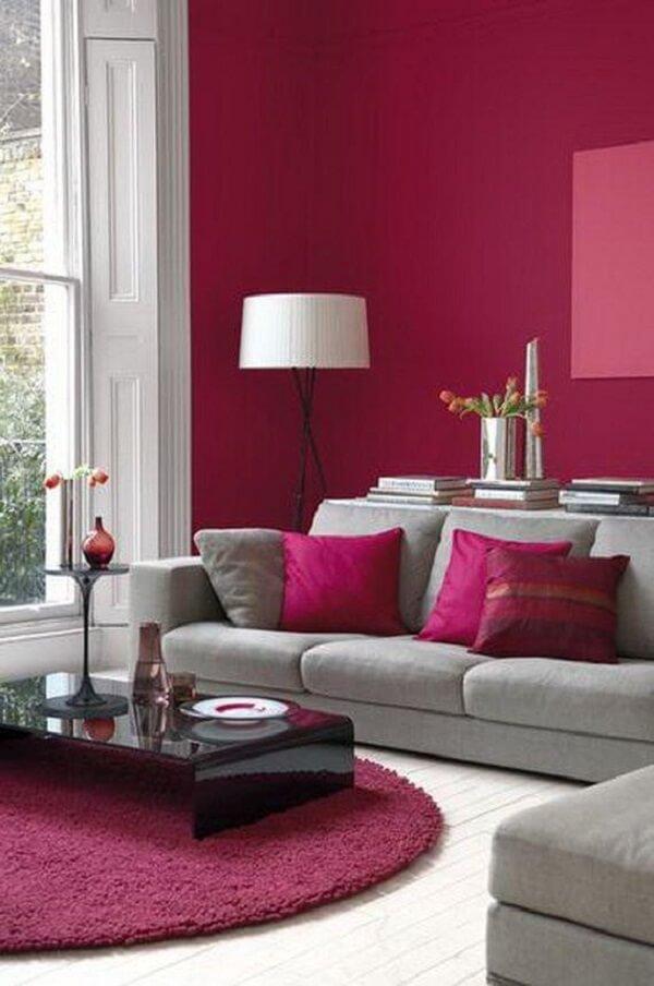 O tapete rosa pink redondo se harmoniza com as almofadas e paredes do ambiente