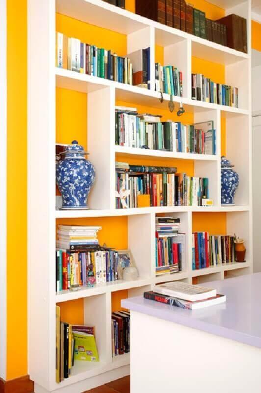 parede amarela decorada com estante branca de nichos  Foto Simone Collet