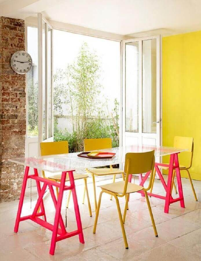 tons de amarelo para parede de sala de jantar decorada com mesa de tampo de vidro e base rosa Foto Webcomunica