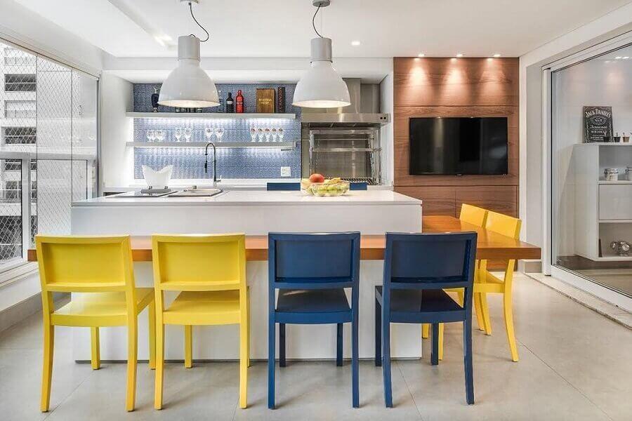 varanda gourmet decorada com bancada de madeira e cadeiras amarelas e azuis  Foto Fernanda Dabbur Arquitetura e Interiores