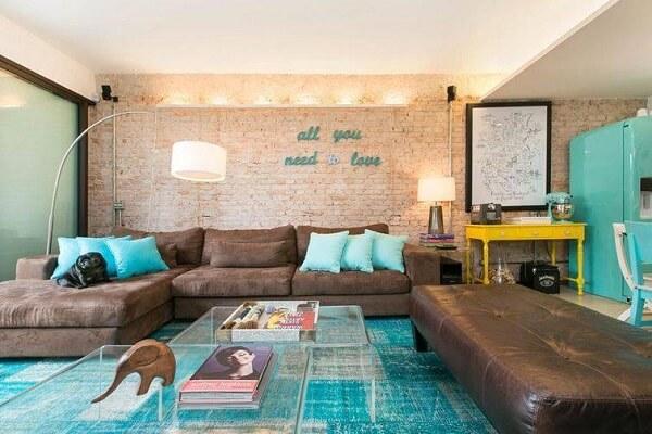 O sofá de canto em tom marrom se conecta com a decoração do ambiente