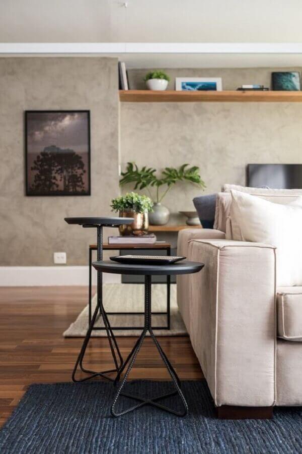 sala moderna decorada com parede de cimento queimado e mesa de canto preta redonda  Foto SP Estúdio