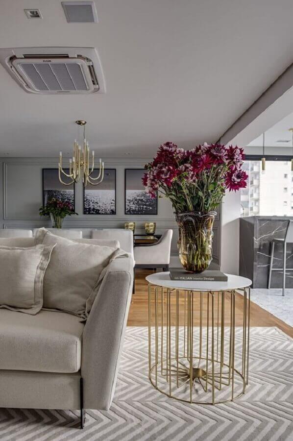 sala sofisticada decorada com mesa de canto redonda dourada  Foto Archzine