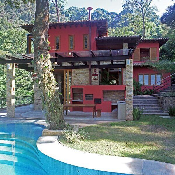 A parede com pintura vermelha realça a beleza das casas de campo simples com varanda
