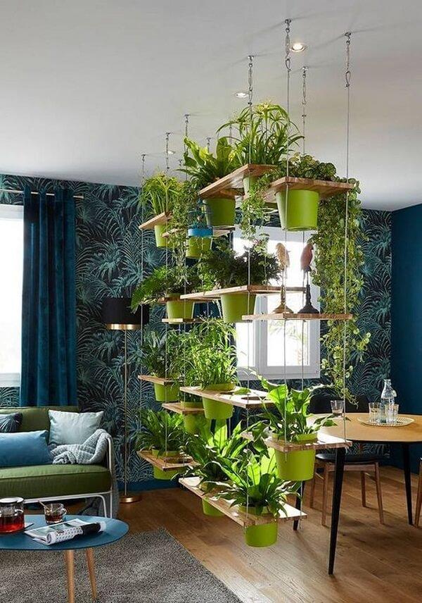 A prateleira moderna serve de divisória de ambiente e sustenta diversos vaso de planta suspenso