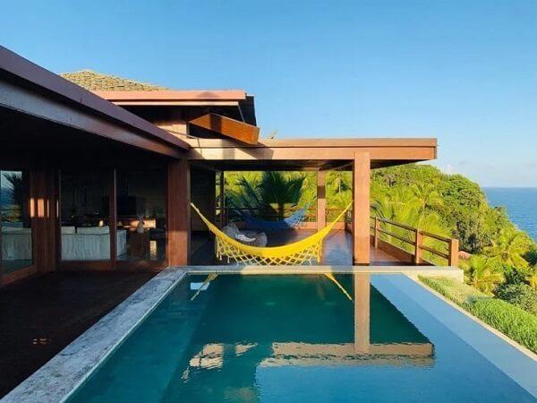 As redes de descanso são ótimas aliadas nos projetos de casas de campo com varanda ao redor