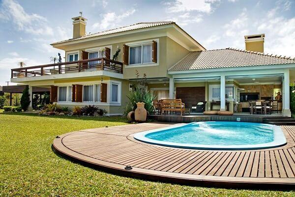 Deck de madeira e vasos cerâmicos fazem parte da decoração de diversas casas de campos com varanda e piscina