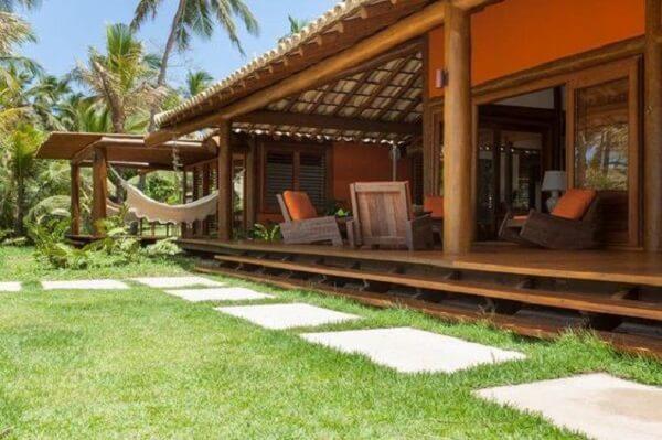 Em casas de campo com varandas mais altas do que o nível do chão, vale a pena colocar degraus em toda sua extensão