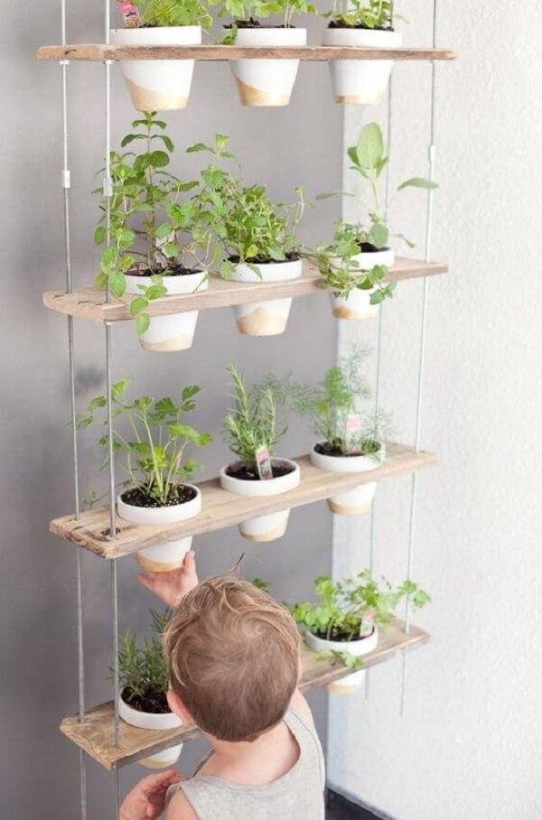 Incentive as crianças a cultivar temperos nos vasos para horta suspensa