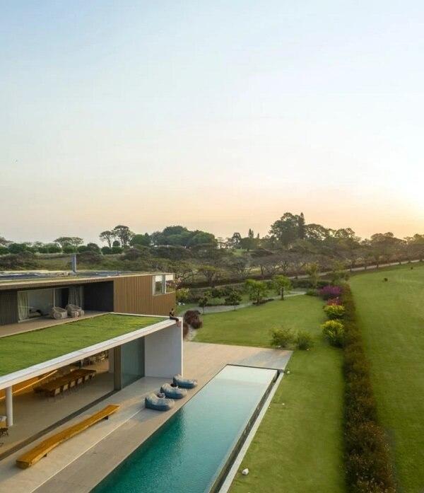 O gramado percorre o entorno das casas de campo com varanda e piscinas