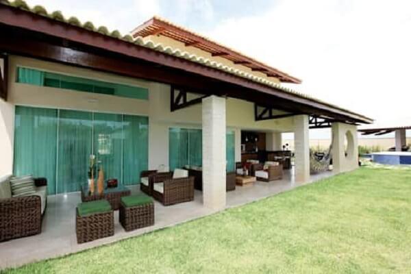 Os sofás são os móveis favoritos para compor a decoração das casas de campo com varanda ao redor