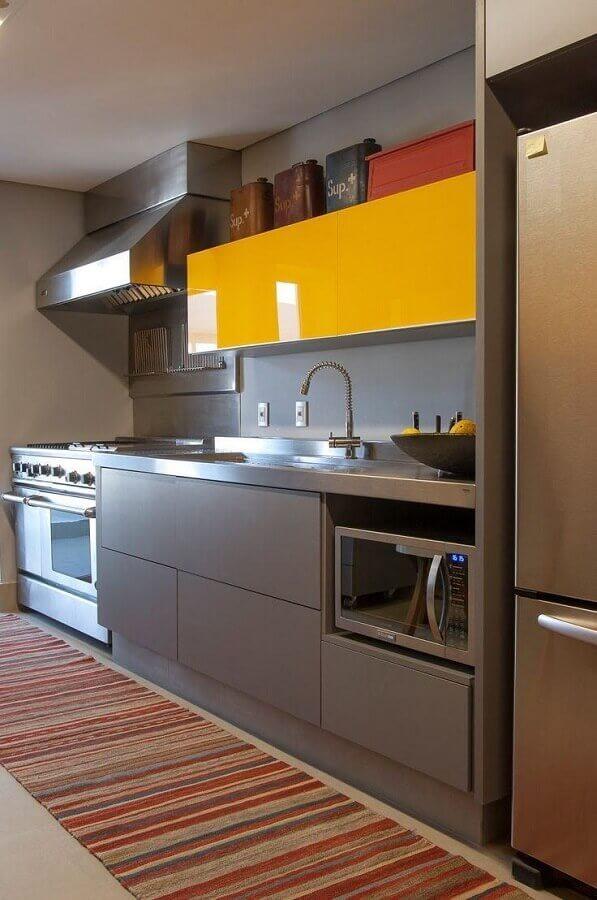 cozinha em tons de cinza decorada com armário aéreo amarelo  Foto AMC - Arquitetura