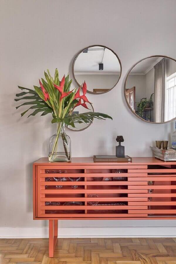 decoração com buffet na cor coral e espelho de parede decorativo redondo  Foto Casa de Valentina