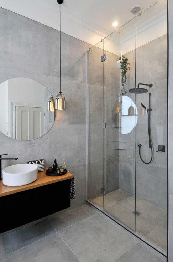 decoração de banheiro em tons de cinza com espelho redondo e gabinete preto com bancada de madeira Foto Apartment Therapy
