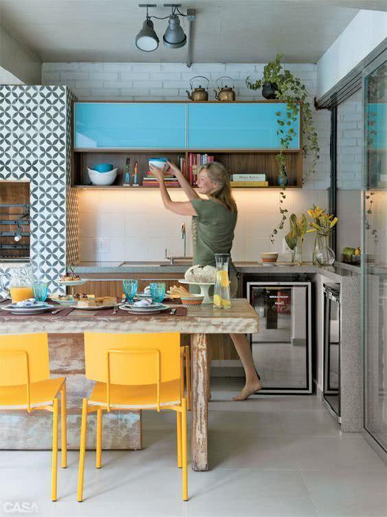 Mesa para varanda gourmet com cadeira amarela em destaque