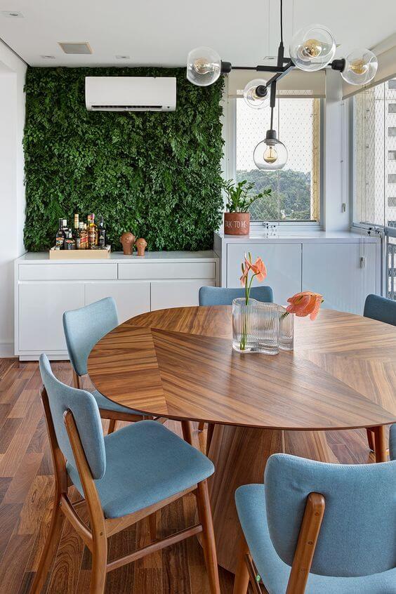 Mesa para varanda gourmet com cadeiras azuis e jardim vertical