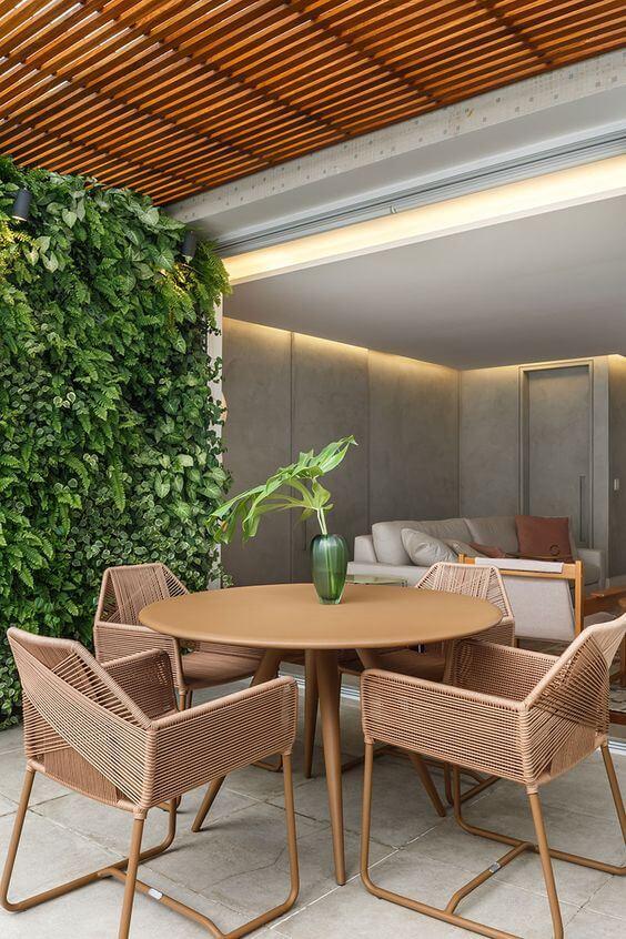 Mesa redonda para varanda gourmet rústica com jardim vertical na decoração