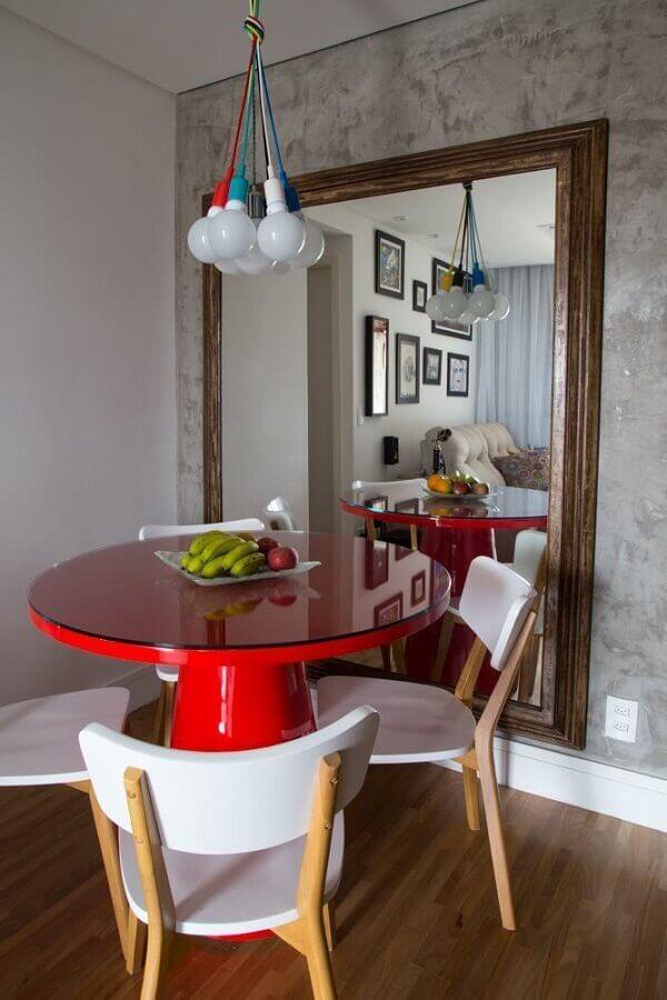 sala de jantar decorada com espelho grande de parede e mesa redonda vermelha  Foto Apartment Therapy