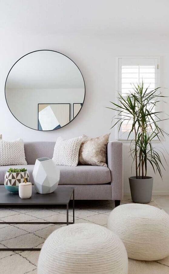 sala minimalista decorada com sofá cinza e espelho de parede redondo Foto Archidea