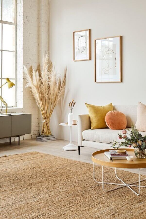 sala simples decorada com almofadas coloridas e tapete sisal bege  Foto Anthropologie