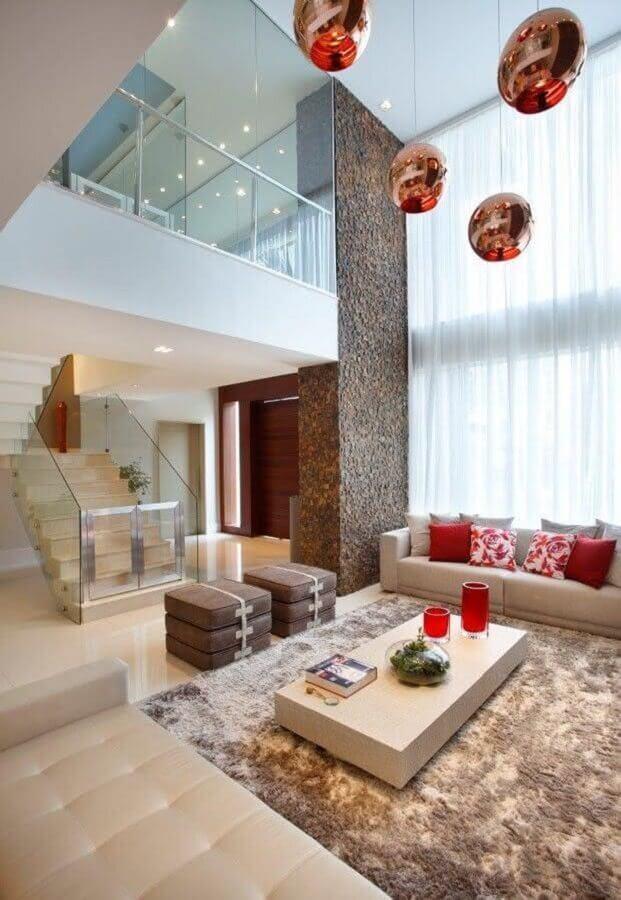 tapete bege mesclado para sala grande decorada em cores neutras com almofadas vermelhas Foto Homify