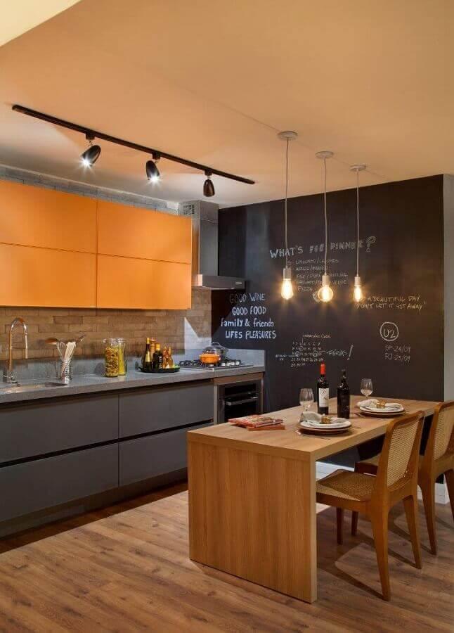 tons de cinza para decoração de cozinha com mesa de madeira e armário aéreo laranja
