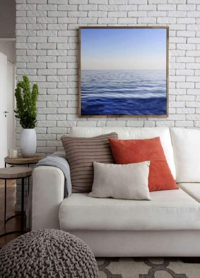 vaso decorativo para sala de estar com parede de tijolinho branca e almofadas coloridas Foto Jeito de Casa