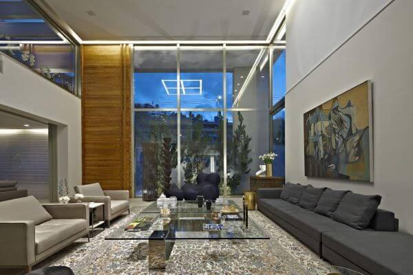 Casa grande com sala em tons de cinza decorada com quadro abstrato e tapete estampado