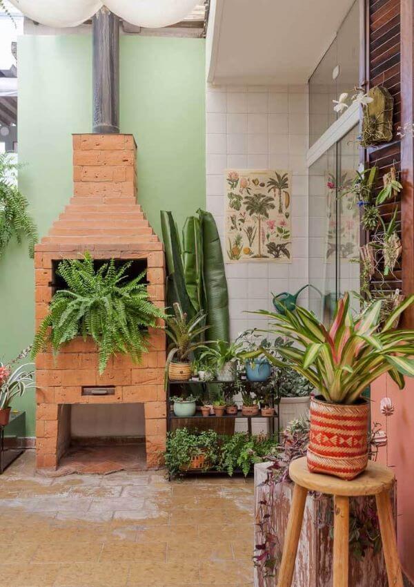 Chaminé de churrasqueira de tijolinho pequena com plantas na decoração