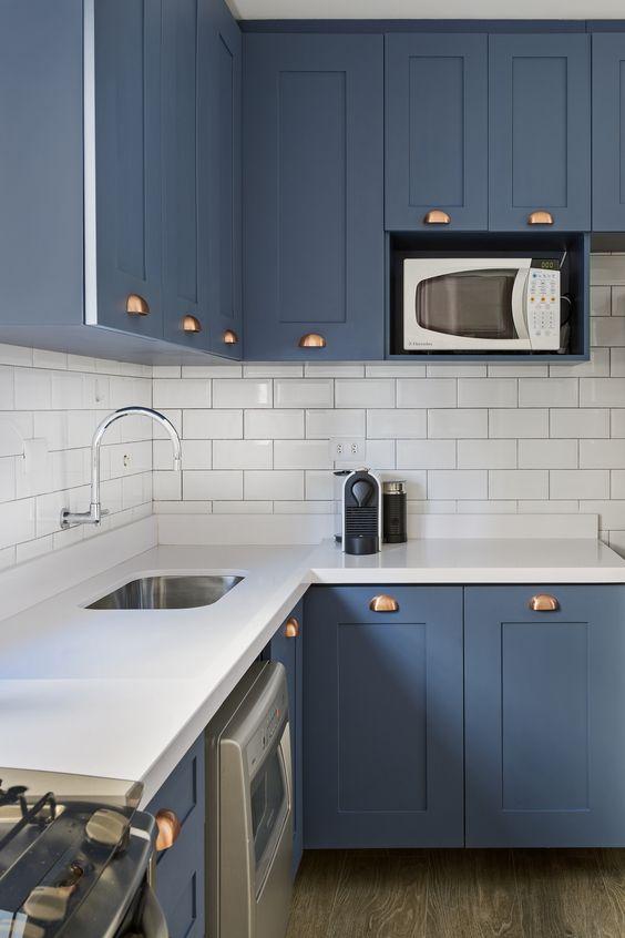Cozinha moderna com silestone branco e armário de canto de parede azuis