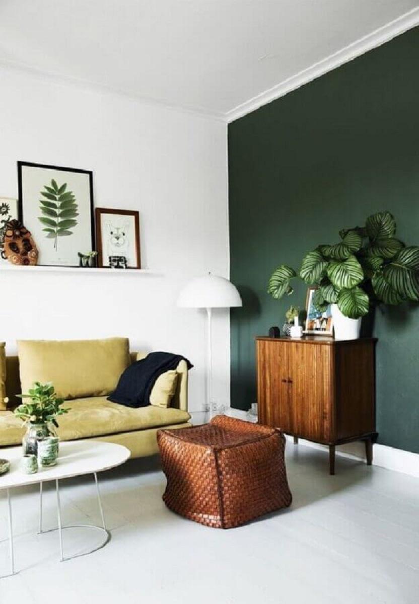 Decoração de sala de estar com parede verde e armário de madeira pequeno