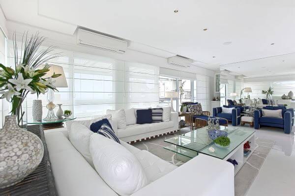 Decoração de sala grande decorada com móveis e detalhes em azul marinho