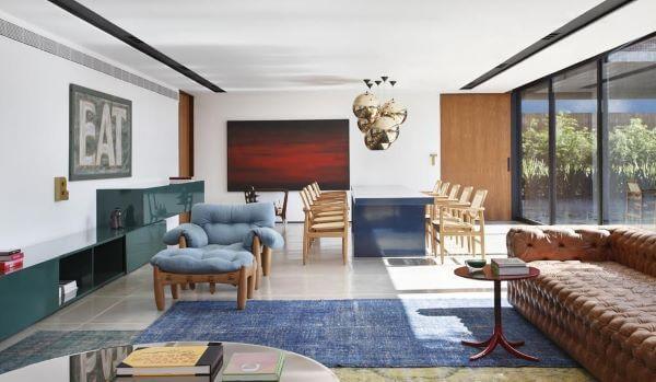 Decoração de sala grande decorada com mesa de jantar azul e sofá chesterfield