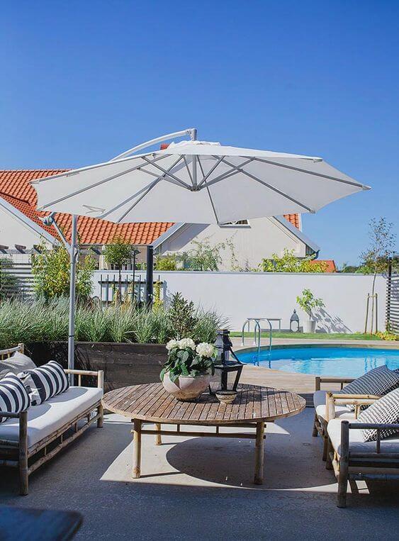 Guarda sol para área da piscina com mesa de madeira e cadeiras confortáveis