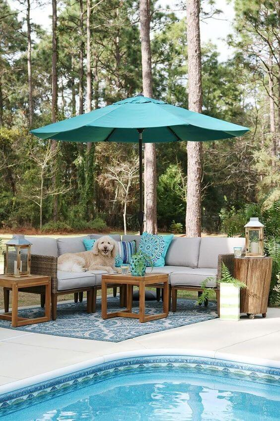 Guarda sol para piscina azul e sofá bege