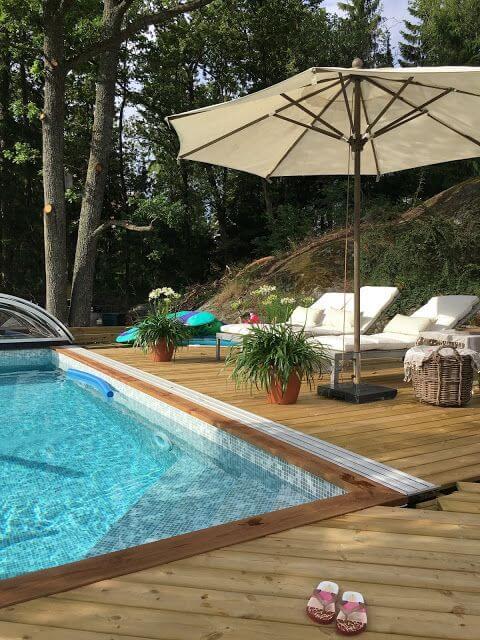 Guarda sol para piscina com espreguiçadeira e deck de madeira moderno