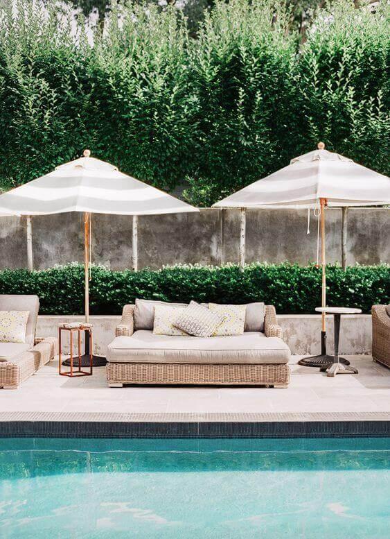 Guarda sol para piscina perto de sofás impermeáveis e caderias para relaxar