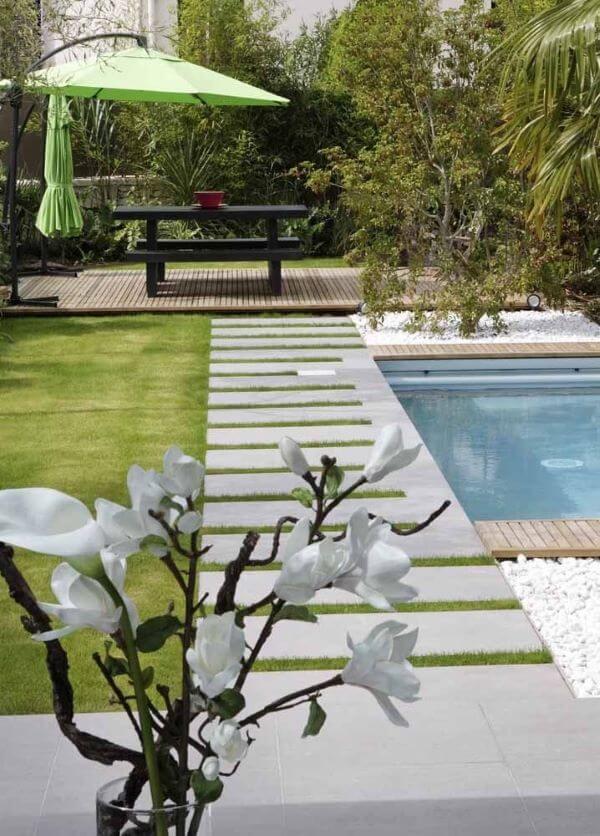 Jardim com guarda sol para piscina verde