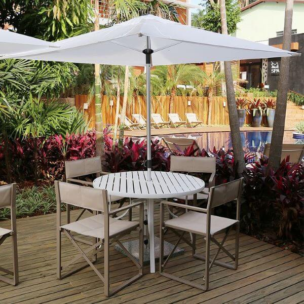 Mesa para área externa com guarda sol grande e branco