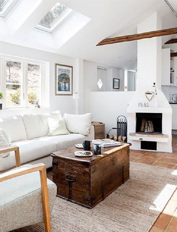 Sala com lareira de chaminé e bau de madeira e tapete bege