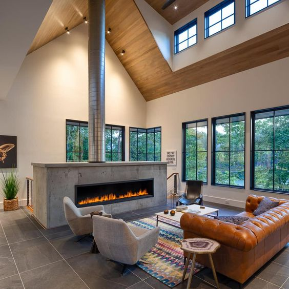 Sala com lareira grande no meio do ambiente e chaminé de inox